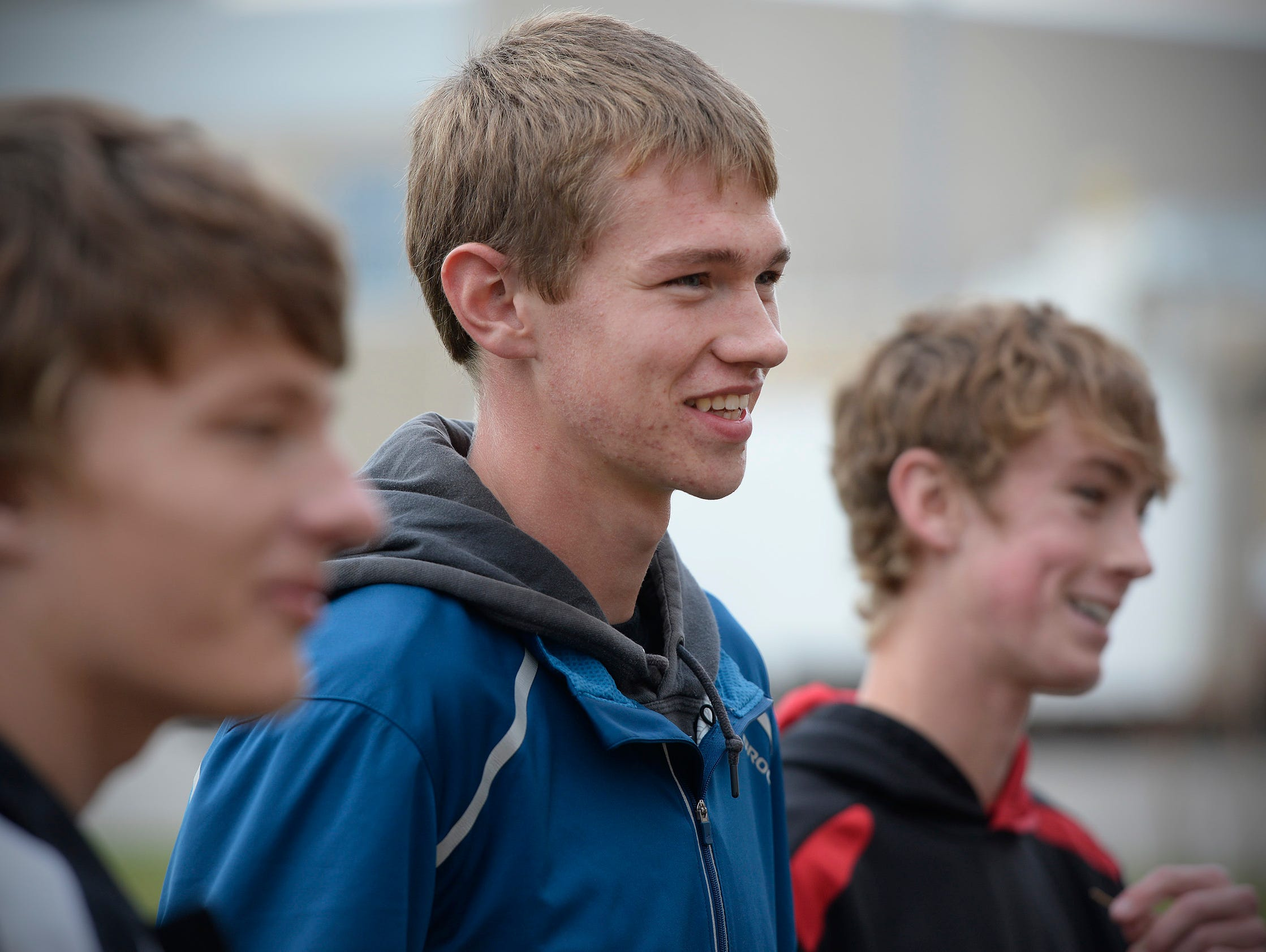 Rocori High School cross country standout Noah Lahr, center, smiles as he and his teammates gather after warmups in practice Tuesday, Oct. 27 at the school.