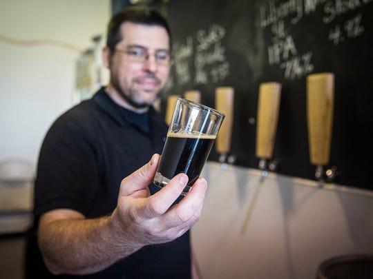 Sean Brady displays one of the beers he crafts at New Corner Brewing Co. in the southside Industria Centre.