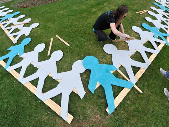 """Every fourth person is painted teal, because one in four girls by her eighteenth birthday will be sexually assaulted,"" said Amber Wagman, a therapist with Turning Point Women's Counseling & Advocacy Center, seen here, helping put together a lawn display. The center helps counsel survivors of child sexual abuse."