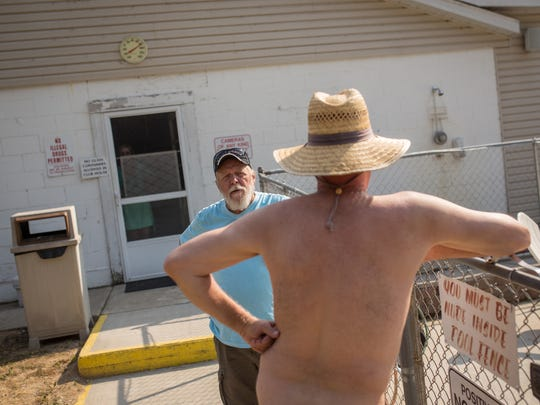 Cherry Lane Nudist Resort owner Dennis Bevis, 66, talks with a resident outside of the pool at Cherry Lane Nudist Resort in North Adams, Michigan, just south of Jackson.