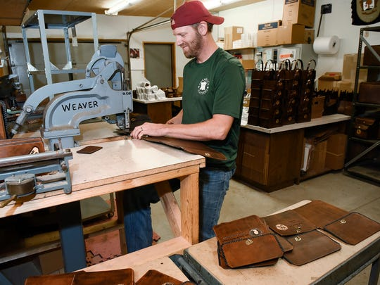 Bryan Brophy, Shamrock Leathers, rivets together custom leather shell bags Wednesday, May 23, at his shop in St. Joseph. Brophy wants to add a trap shooting range to his new leather shop.