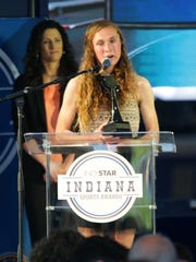 Carmel's Sarah Leinheiser accepts the trophy for girls' cross-country runner of the year at the Indiana Sports Awards at Lucas Oil Stadium, April, 28, 2016.