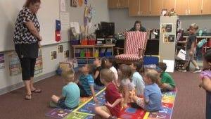 Teacher Monica Shook gets children settled down at Buckeye's new preschool.