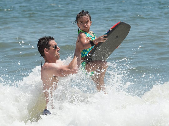 Jeff O'Hara of Reading, Pa., lifts his daughter Riley (6) over a wave at Rehoboth Beach.