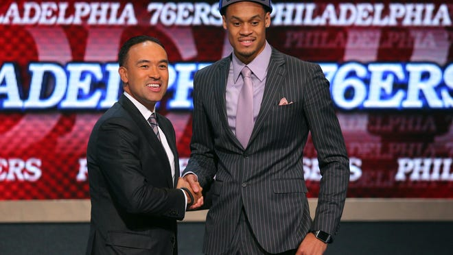 Clemson's K.J. McDaniels, right, shakes hands with NBA deputy commissioner Mark Tatum after being selected with the 32nd overall pick to the Philadelphia 76ers in the second round of the NBA Draft Thursday in Brooklyn, N.Y.