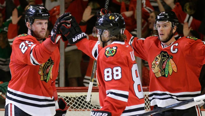 Chicago Blackhawks' Bryan Bickell (29), left, celebrates with Patrick Kane (88) and Jonathan Toews (19) after scoring his goal against the Minnesota Wild during the second period  in Game 5 of an NHL hockey second-round playoff series in Chicago,Sunday, May 11, 2014.