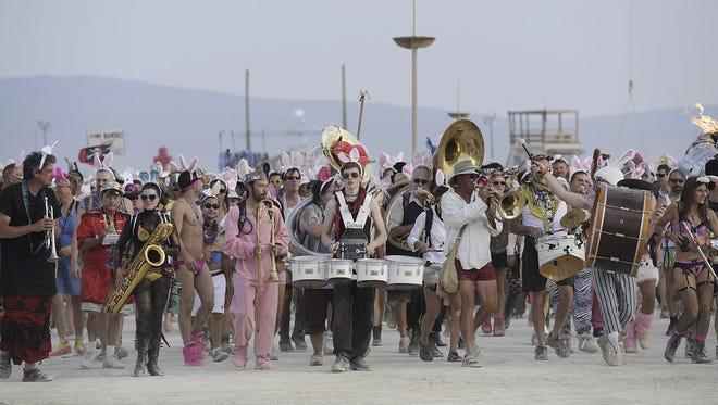 Burning Man participants march on the Black Rock Desert playa last year.