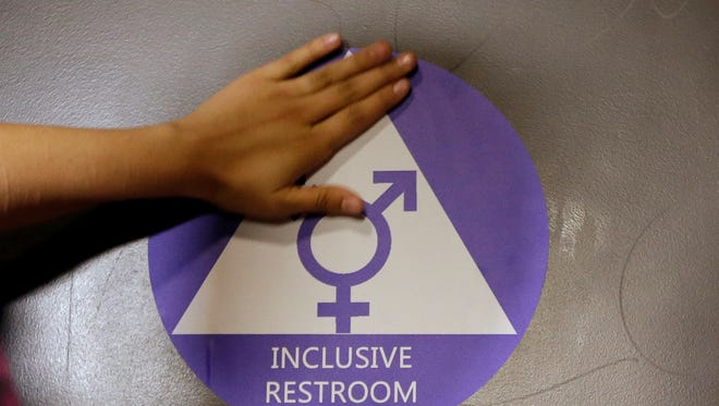 A new sticker is placed on the door at the ceremonial opening of a gender neutral bathroom at Nathan Hale High School in Seattle in May 2016.