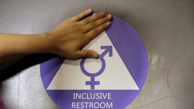 A new sticker is placed on the door at the ceremonial opening of a gender neutral bathroom at Nathan Hale High School in Seattle lin 2016.