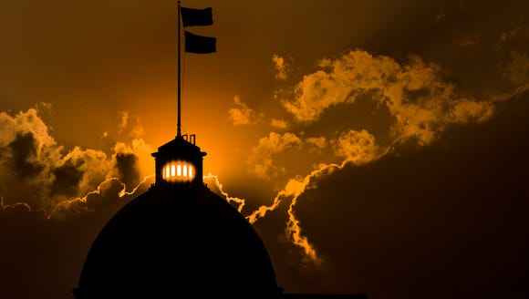 The sun sets behind the Alabama State Capitol Building