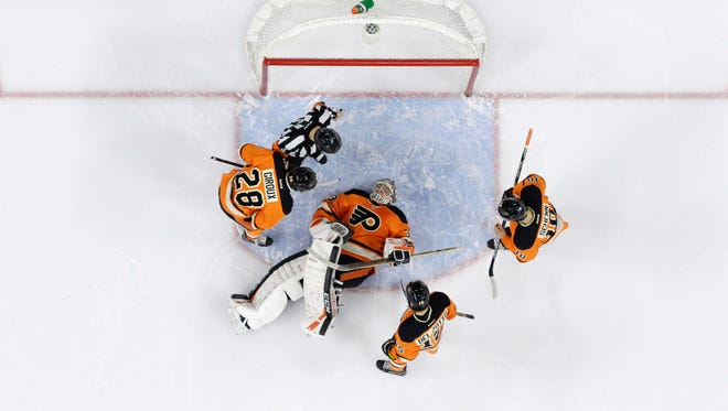Philadelphia Flyers goalie Steve Mason lies injured on the ice after making a leg save.