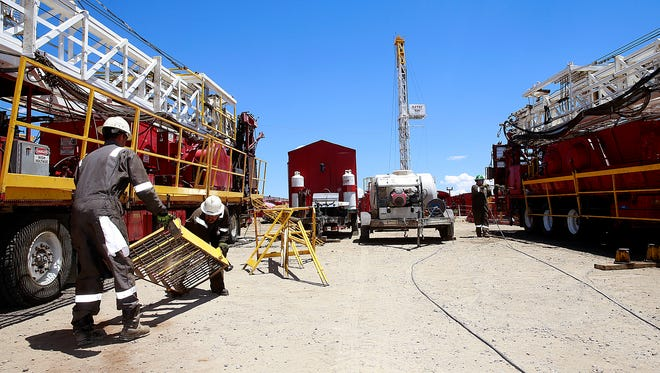 Workers service workover rigs on Thursday at Aztec Drilling in Aztec.