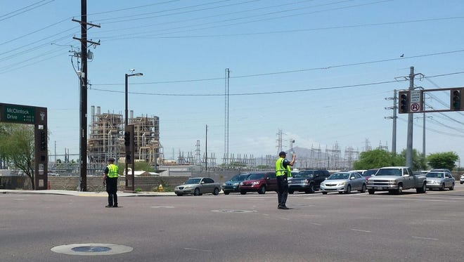 Tempe police officers direct traffic in the intersection of McClintock and University drives after a transformer fire knocked out power for thousands on June 29, 2015.