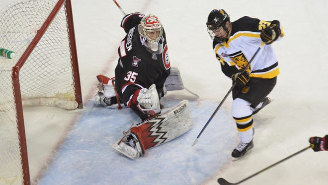 St. Cloud State's Charlie Lindgren (35) watches a rebound head wide of the net as Colorado College's Matt Hansen pursues it Friday in Colorado Springs, Colorado.