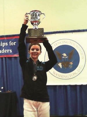 Maggie Snider holds the championship trophy at the USA Fencing Division II Women's Epee competition in April 2014. She won the North American Cup gold medal, which featured more than 110 competitors, at age 13.