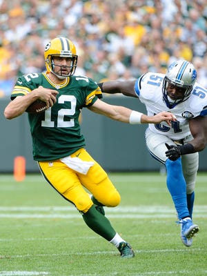 Packers quarterback Aaron Rodgers scrambles away from the Lions' Brandon Copeland in the third quarter.