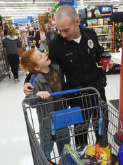 Evan Holt, 10, of Mountain Home, shares a smile with Mountain Home Police Officer Mychal Warno.