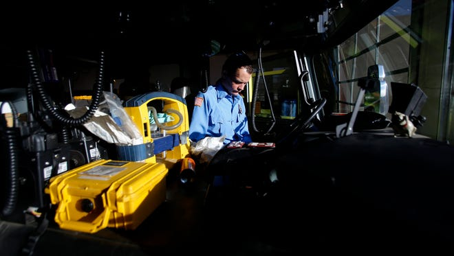 Engineer Ian Rutter goes through a check list Friday inside the cab of a fire engine at the Bloomfield Fire Department.