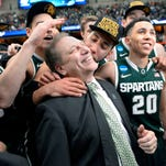 MSU head coach Tom Izzo gets a hug and kiss  from player Denzel Valentine, center, with players Gavin Schilling, left,   and Travis Trice, right, after MSU's 76-70 win over Louisville in their NCAA Elite Eight  game in Syracuse, NY Sunday 3/29/2015.  MSU now heds to Indianapolis for the Final Four.