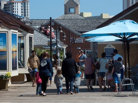 Visitors to the Pensacola Beach boardwalk window shop while out for a stroll March 21.