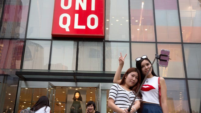 Chinese women take a selfie outside the Uniqlo flagship store where a steamy video purportedly taken inside one of its fitting room showing a couple apparently having sex in Beijing, Thursday, July 16, 2015. While online searches for the Japanese clothing brand soared after the viral spread of the video, it has also drawn the concern of the police and China's highest web regulator who are investigating whether it was a vulgar marketing gimmick. (AP Photo/Ng Han Guan)