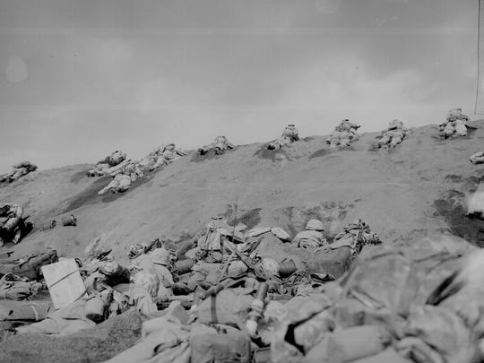 Members of the 5th Marines inch up a slope on Red Beach on Iwo Jima.