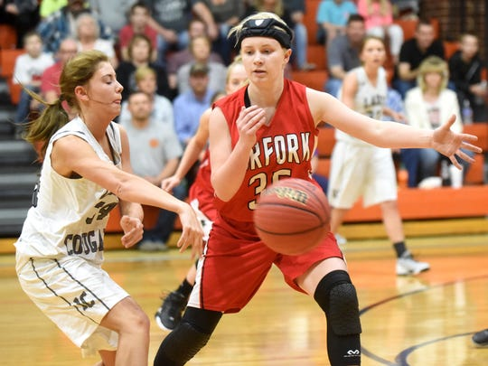Norfork's Kinley Stowers, right, goes for a steal against Izard County's Jen King.