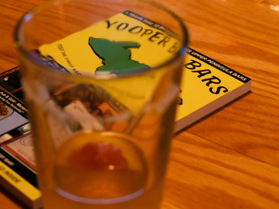 "The book ""Yooper Bars"" sits on a bar counter inside"