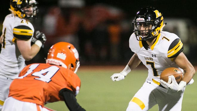 Red Lion's Giuliano Favorito (right) looks for yardage against Central York on Friday night. The Lions remained unbeaten with a 28-18 victory, but they were seriously tested for the first time all year. Amanda J. Cain photo
