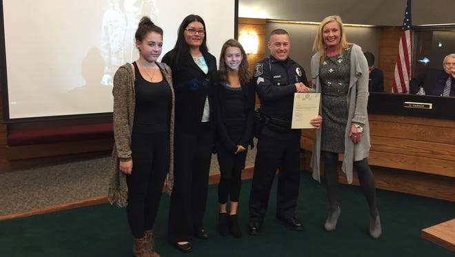 Howell Police Officer Mike Dunn is honored for his contributions to Project Opiate, which includes jail-based counseling and community education events, at a Monday night Livingston County Board of Commissioners meeting. He is joined by (left to right) his daughter Mikaela, 13, wife Magdalena, daughter Marissa, 11, and District Court Administrator Francine Zysk.