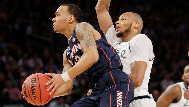 Connecticut's Shabazz Napier, left, goes up to shoot past Michigan State's Adreian Payne in a regional final of the NCAA Tournament on Sunday.