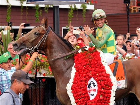 Javier Castellano smiles in the winner's circle after Keen Ice defeated Triple Crown winner American Pharoah to win the Travers Stakes horse race at Saratoga Race Course in Saratoga Springs, N.Y., Saturday, Aug. 29, 2015.