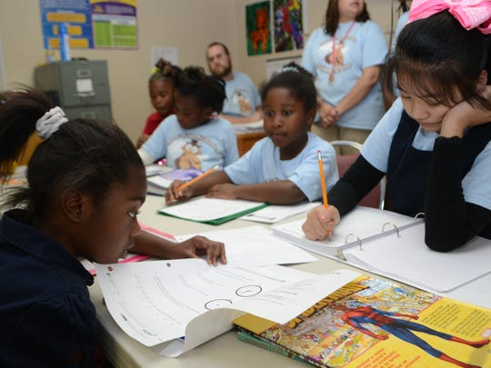 "Mia Gibson (left), Tina Wang and Ka'Martah Richard do homework at the Pineville Youth Center. The youth center was participating in the nationwide celebration of afterschool programs called ""Lights On After School."""