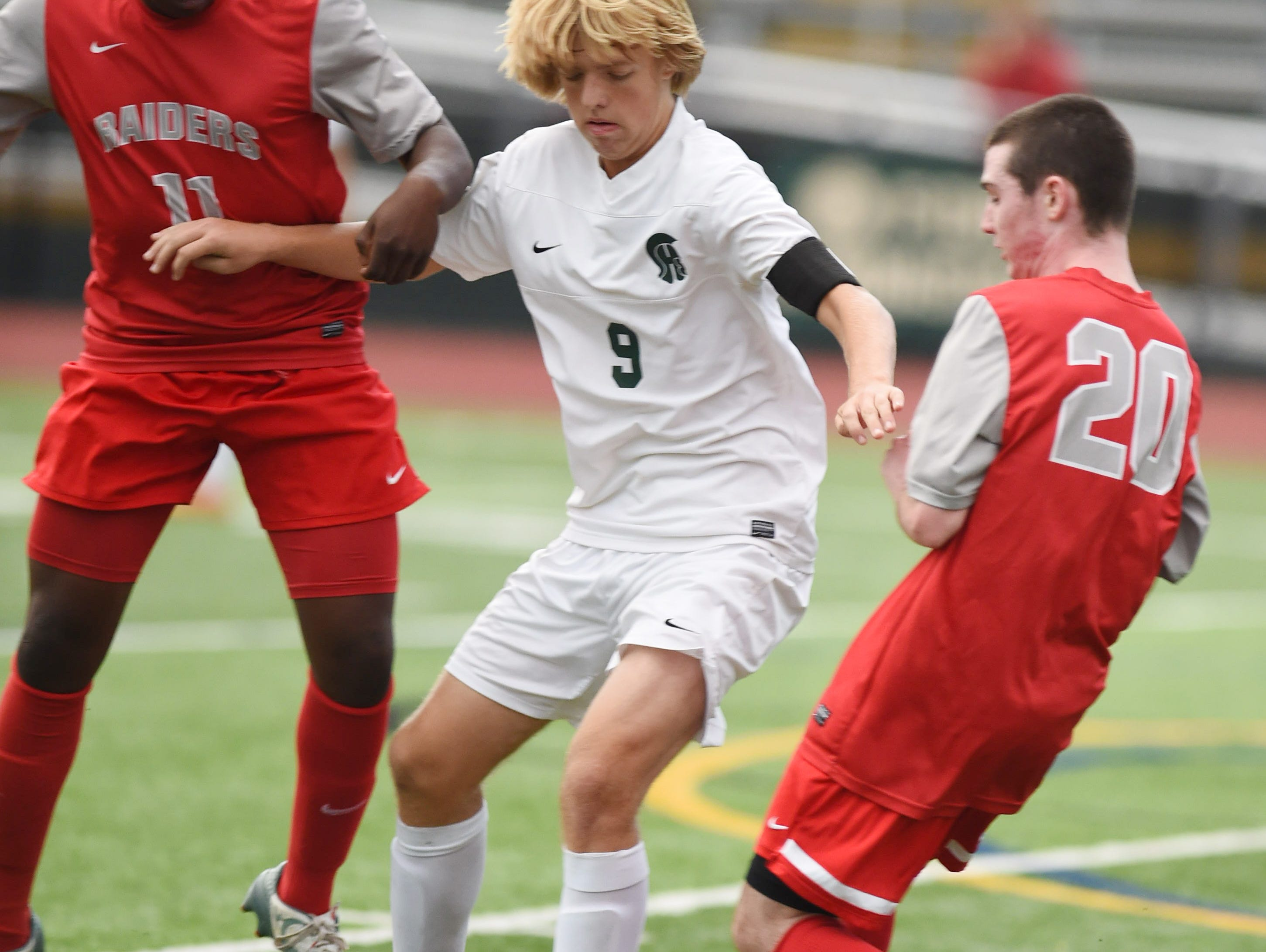 Spackenkill's Jake Kaufman, center, attempts to fend off Red Hook's, from left, Jeff Kiluba and Liam Jantzen on Oct. 22, 2015 in Staatsburg.