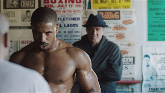 "Michael B. Jordan (center) and Sylvester Stallone (right) in a scene from ""Creed."""