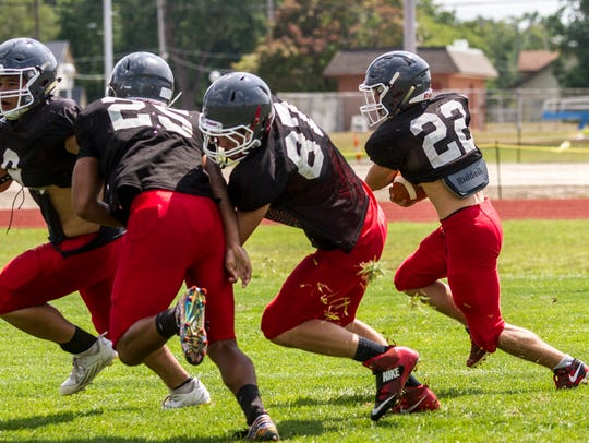The Port Huron Big Reds run drills during practice