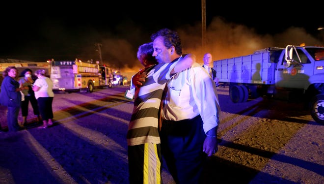 New Jersey Gov. Chris Christie, right, is hugged by Michael Cisneros, 14, during a visit to the massive fire on the Seaside Park boardwalk, Thursday.