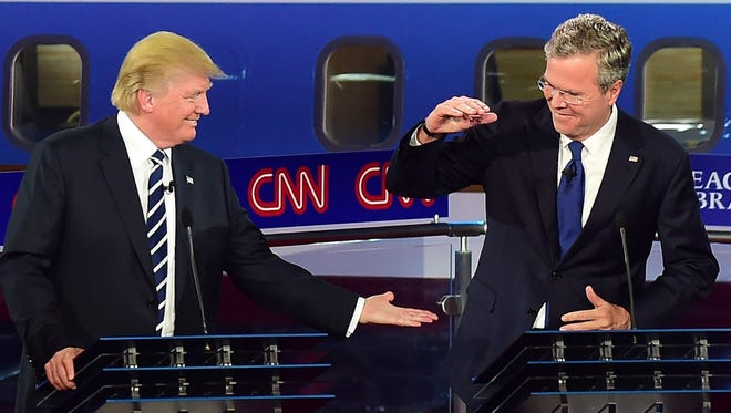 Republican presidential hopefuls Donald Trump (L) and Jeb Bush high five during the Republican Presidential Debate  at the Ronald Reagan Presidential Library in Simi Valley, California on September 16, 2015.  Republican presidential frontrunner Donald Trump stepped into a campaign hornet's nest as his rivals collectively turned their sights on the billionaire in the party's second debate of the 2016 presidential race.