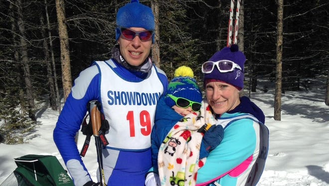 David Holien, winner of the classic race, and his wife Laura, winner of the skate ski race, relax after the race with their young son, Chuck.