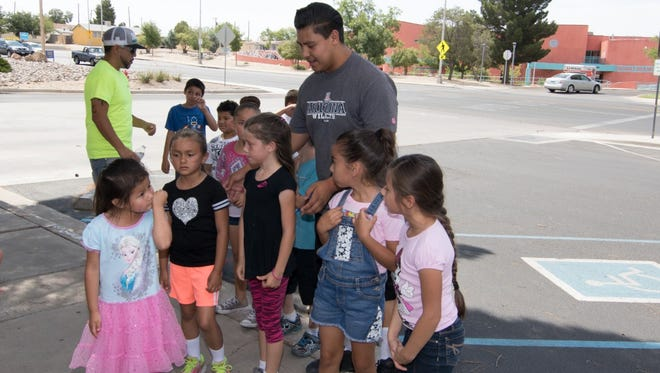Roman Garcia keeps youngsters in line as they arrive at their field trip destination to the fire station as part of the Safe Haven Weed and Seed program.