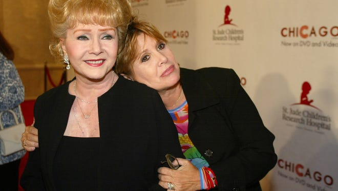 """FILE - In this Tuesday, Aug. 19, 2003 file photo, Debbie Reynolds and Carrie Fisher arrive at the """"Runway for Life"""" Celebrity Fashion Show Benefitting St. Jude's Children's Research Hospital and celebrating the DVD relese of Chicago in Beverly Hills, Calif. On Tuesday, Dec. 27, 2016, a publicist said Carrie Fisher has died at the age of 60. (AP Photo/Jill Connelly, File)"""