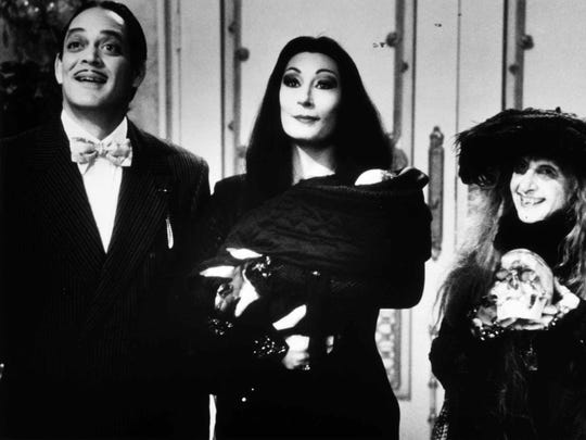 Anjelica Huston as Morticia Addams and Raul Julia as Gomez Addams.