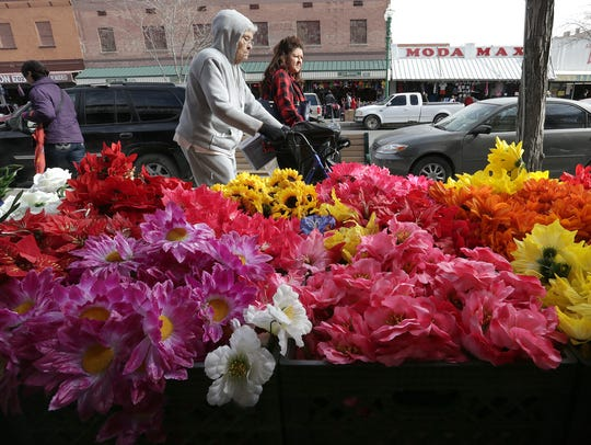Shoppers stroll past New York Trading on El Paso Street,