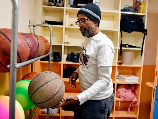 Louis Woodyard puts away basketballs Wednesday, April