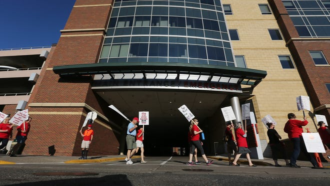 Thousands of nurses walk around Abbott Northwestern hospital on the first day of a strike Sunday, June 19, in Minneapolis. About 4,800 nurses at five Minneapolis-area hospitals, all operated by Allina Health, began a weeklong strike Sunday over a contract impasse.