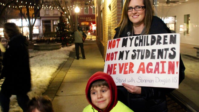 A woman and her two children hold up a homemade sign at the rally in downtown Milford.
