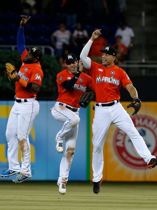 Miami Marlins' Marcell Ozuna, left, Christian Yelich, center, and Giancarlo Stanton celebrate after they defeated the Arizona Diamondbacks in a baseball game, Sunday, June 4, 2017, in Miami. (AP Photo/Wilfredo Lee)