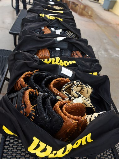 A row of bags filled with various types of Wilson gloves