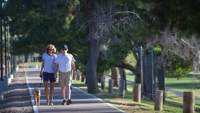 Early morning walkers take to Scottsdale's Indian Bend Wash Greenbelt on Thursday, May 22, 2014. The city budgets for risk management, in part to settle lawsuits from employees and residents who are injured. A recent payout included $140,000 in taxpayer money to a resident who fell and was injured while riding his bike down the Indian Bend Wash path.