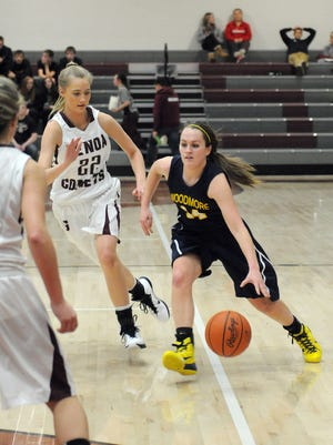 Woodmore's Lily Rothert (#14) tries to outrun Genoa's Erica Harder (#22) to make a basket during the Wildcats game at Genoa Area High School on Tuesday night.